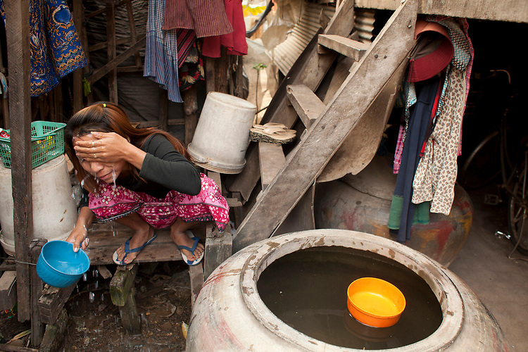 A young woman washes her face in a small village near Battambang, Cambodia. <br /> <br /> Photos &copy; Dennis Drenner 2013.