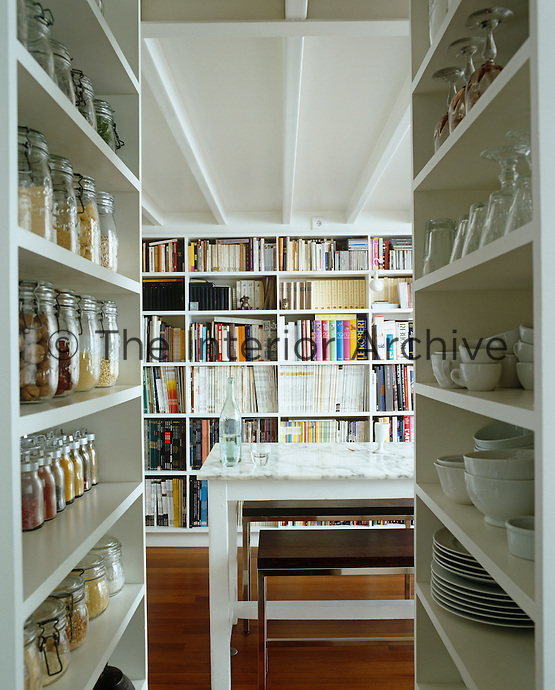 This passageway leading to a small dining area has rows of painted shelves stacked with matching Kilner jars, white china and wine glasses