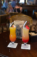 Two glasses of Sling cocktail (Spring sling and Summer sling) at the table of historic Long bar in Raffles hotel, Singapore.