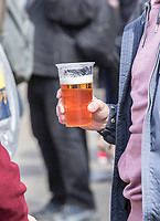 Male hand holding a plastic cup filled with freshly tapped Beer, showing part of the males purple hoodie and blue jacket. Blurred background