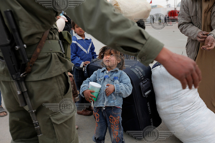 Four year old Nermine cross with her family into Tunisia, holding water and supplies they just have been given. Tens of thousands of people, mainly Egyptian workers, flee unrest in Libya and cross the border into Tunisia. Some slept in the open for several days before being processed.  At the same time forces loyal to Col. Gaddafi fought opposition forces in various parts of the country.