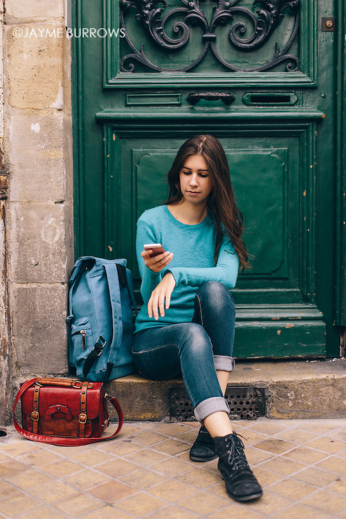 Portrait of a young student waiting and looking at her phone.