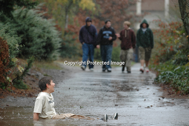 Mason Brangwin, a freshman at Shorewood High School, sits in a massive puddle that formed after a storm drain was plugged, in response to a bet from friends November 11, 2005. Brangwin received $20.00 for completing the task.