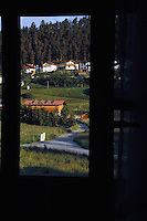 View from window overlooking narrow road,farmland and homes.  Imst district, Tyrol/Tirol, Austria, Alps.