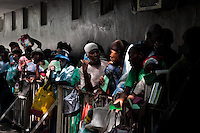Haitian people wait in a line to be given food for free in a feeding center in Port-au-Prince, Haiti, 17 July 2008.