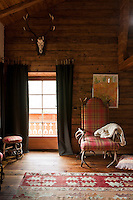 A hunting trophy hanging above the window in the living room complements the high-backed chair and footstool