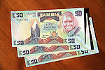 3 Zambian 50 kwacha currency bills on table