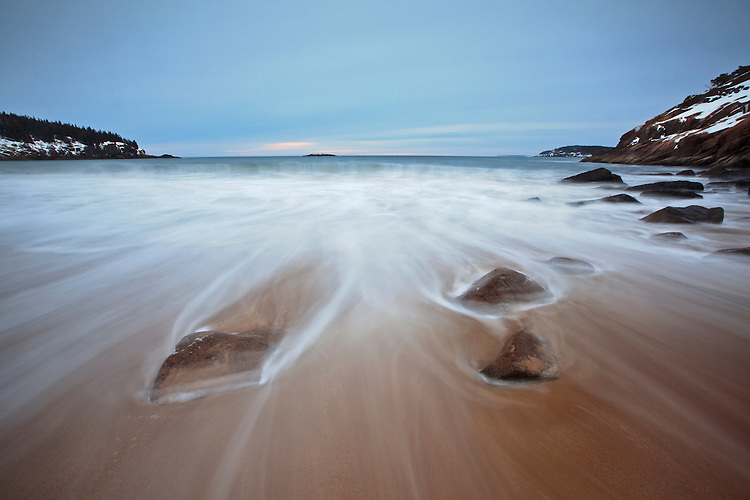Waves swirl around the rocks at Sand Beach in winter in Acadia National Park, Mount Desert Island, Maine, USA
