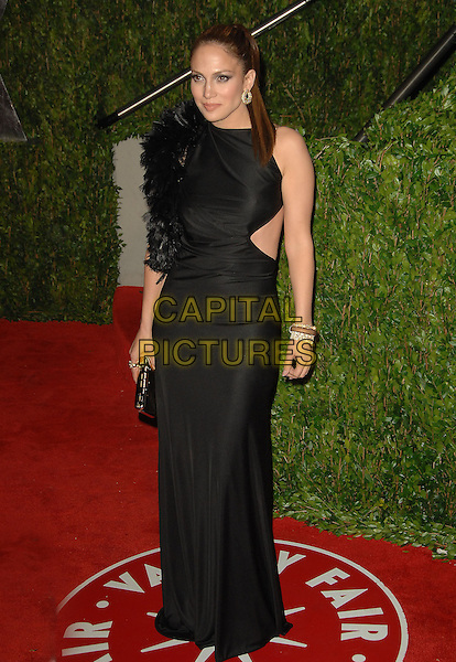 JENNIFER LOPEZ.The 2010 Vanity Fair Oscar Party held at The Sunset Tower Hotel in West Hollywood, California, USA..March 7th, 2010.oscars full length black maxi dress silk satin cut out sides sleeveless feathers .CAP/RKE/DVS.©DVS/RockinExposures/Capital Pictures.