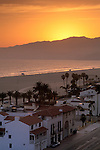 Sunset over coastal mountains and homes along sand beach at Santa Monica, Los Angeles County, California