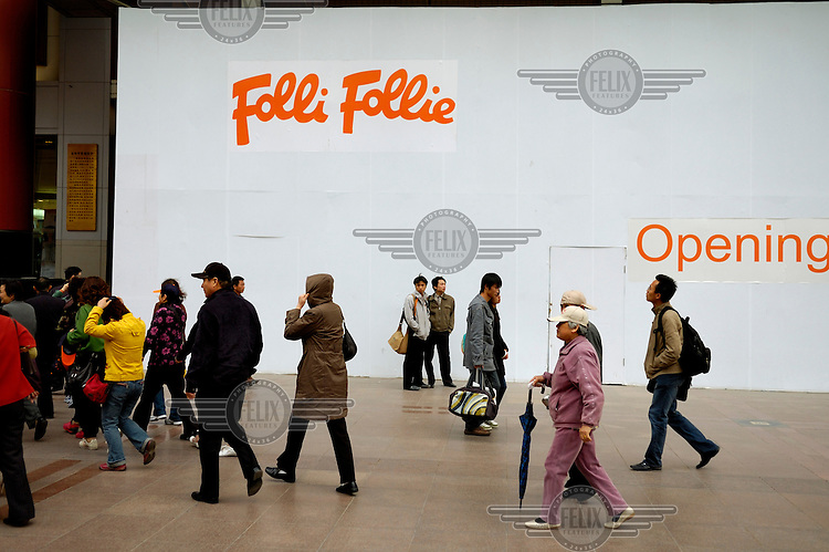 Shoppers on Wangfujing pass a hoarding advertising the opening of a new Folli Follie fashion store.