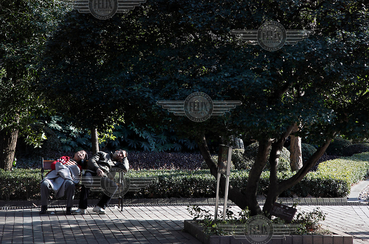 A man and a women asleep together on a bench in the People's Park.