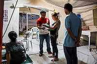 Nurse Sharon Pacaldo, of Philippine Red Cross, looks at a severely dehydrated child patient's file in the medical tent for evacuees in the city's largest stadium in Zamboanga, Mindanao, The Philippines on November 4, 2013. These Internally Displaced People (IDP) had taken refuge in this stadium after surviving the 3 week long attack by MNLF rebels. Photo by Suzanne Lee for SPRINT-IPPF