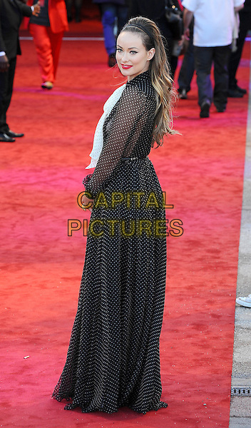 "Olivia Wilde .The UK Premiere of ""Cowboys And Aliens"", O2 Arena, London, England..11th August 2011.full length black white pussybow sheer polka dot dress side panel hairband looking over shoulder . CAP/BEL.©Tom Belcher/Capital Pictures."