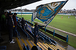 A home fan waving a big flag as Port Talbot Town (in blue) play host to Caerau Ely in a Welsh Cup fourth round tie at the Genquip Stadium, formerly known as Victoria Road. Formed by exiled Scots in 1901 as Port Talbot Athletic, they competed in local and regional football before being promoted to the League of Wales  in 2000 and changing their name to the current version a year later. Town won this tie 3-0 against their opponents from the Welsh League, one level below the welsh Premier League where Port Talbot competed, watched by a crowd of 113.
