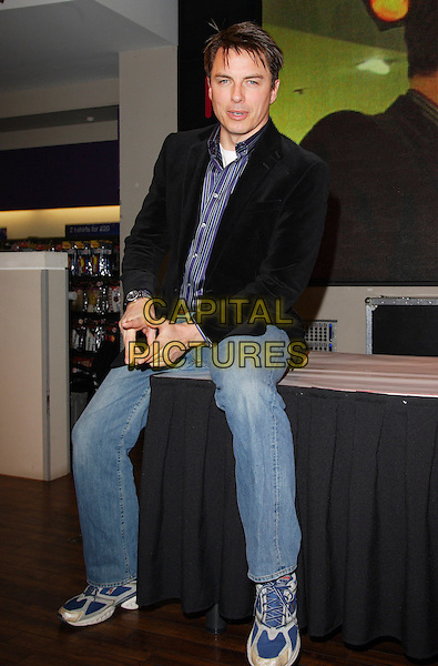"JOHN BARROWMAN.Signing his new album ""Another Side"" at HMV, Oxford Street, London, England..November 16th, 2007.full length black jacket blue shirt striped stripes jeans denim sitting sneakers trainers .CAP/ROS.©Steve Ross/Capital Pictures"