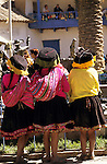 Paucartambo, Peru. Three women wearing traditional clothes and hats from the back.