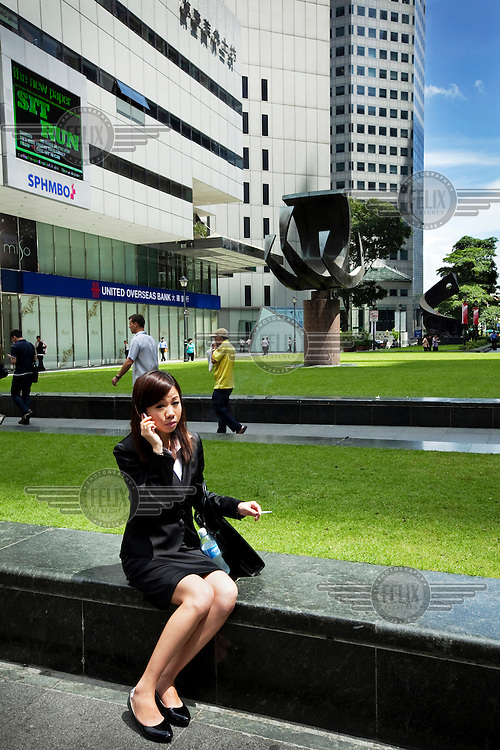 A businesswoman smokes a cigarette whilst she talks on her mobile phone at Raffles Place, the centre of the main business district of Singapore.