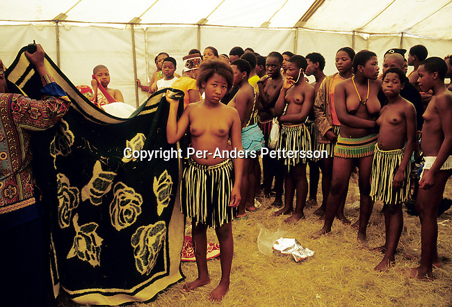 NONGOMA, SOUTH AFRICA - SEPTEMBER 11: Unidentified girls wait to tested for their virginity during the annual Reed Dance on September 11, 2004 in Nongoma in rural Natal, South Africa. About 20.000 maidens from all over South Africa arrived to dance for Zulu King Goodwill Zwelethini at the Enyokeni Royal Palace in Kwa-Nongoma about 350 kilometers from Durban. The girls come to the kingdom to declare their virginity and the ceremony encourages girls and young women to abstain from sexual activity to curb the spread of HIV-Aids..(Photo: Per-Anders Pettersson).....