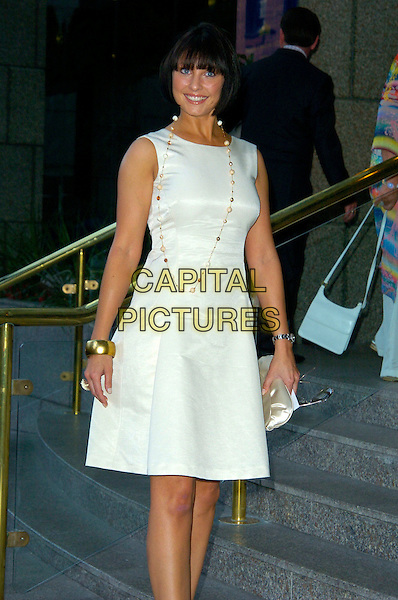 EMMA BARTON.Attending Barbara Windsor's 70th Birthday Party, .Royal Garden Hotel, London, England, August 5th 2007..half 3/4 length grey suit white shift dress cream gold bracelet.CAP/CAN.©Can Nguyen/Capital Pictures
