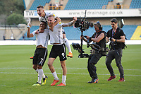 Jefferson Montero (right) Bersant Celina (centre) and Oli McBurnie (left) of Swansea City celebrate at full time of the Sky Bet Championship match between Millwall and Swansea City at The Den in London, England. September 1, 2018