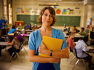 A teacher stands in the front of her classroom holding a notebook wile her students work hard behind her