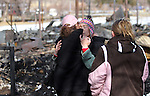 Neighbors comfort Jeannie Watts after her mother died and her house, barn and horses were destroyed by Thursday's wind-driven brush fire in Pleasant Valley. The Watts returned to their home Saturday, Jan. 21, 2012 to survey the damage. .Photo by Cathleen Allison