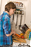 Teenage boy at home in kitchen food preparation peeling carrots vertical Caucasian age 14