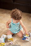 13 month old baby girl at home playing with nesting stacking boxes putting one inside the other concept inside or smaller than vertical