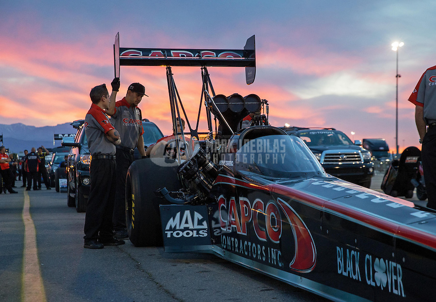 Apr. 5, 2013; Las Vegas, NV, USA: The sun sets behind the car and crew members of NHRA top fuel dragster driver Steve Torrence in the staging lanes during qualifying for the Summitracing.com Nationals at the Strip at Las Vegas Motor Speedway. Mandatory Credit: Mark J. Rebilas-