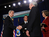 United States President George W. Bush shakes hands with Secretary of Agriculture Ed Schafer during his Ceremonial Swearing-in at the U.S. Department of Agriculture in Washington on February 6, 2008. Looking on are Charles F. Conner, deputy secretary of Agriculture, and Schafer's wife Nancy.  <br /> Credit: Roger L. Wollenberg / Pool via CNP