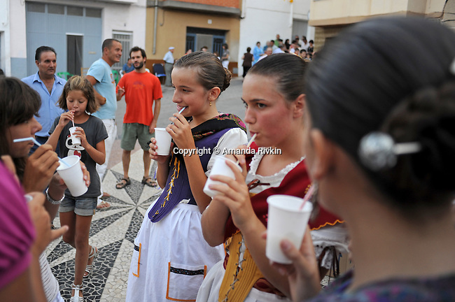 Young girls in traditional attire of the Valencian region drink lemon sorbet after performing in the main square during the municipal fiestas in the town of Costur, Spain on August 15, 2009.