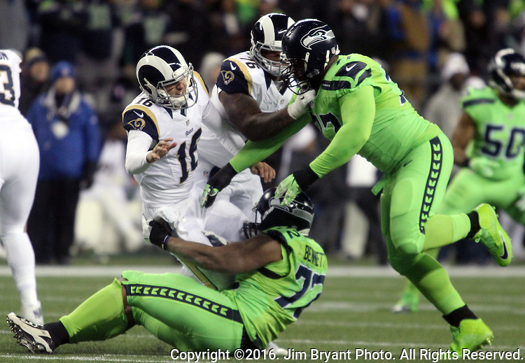 Los Angeles Rams quarterback Jared Goff (16) hits after passing under pressure from Seattle Seahawks defensive end Michael Bennett (72) and  defensive tackle Ahtyba Rubin (77) at CenturyLink Field in Seattle, Washington on December 15, 2016.  The Seahawks beat the Rams 24-3.  ©2016. Jim Bryant Photo. All Rights Reserved