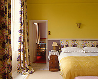 This bedroom has a purple and yellow colour scheme with floral curtains