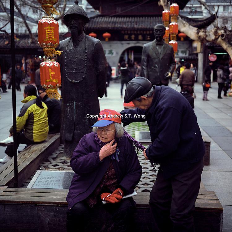An elderly Chinese man wraps a scarf around his wife's neck in Nanjing, Jiangsu province, 2012. (Mamiya 6, 75mm f3.5, Kodak Ektar 100 film)