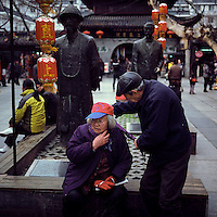 An elderly Chinese man wraps a scarf around his wife's neck in Nanjing, Jiangsu province, 2012. (Mamiya 6, 75mm f3.5, Kodak Ektar 100 film)