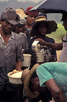 Child labor at sugarcane cutting - workers stand in line in the field for receiving a meal at lunch time - food served with no tableware, no protection against sun or rain. Bahia State, Northeastern Brazil.