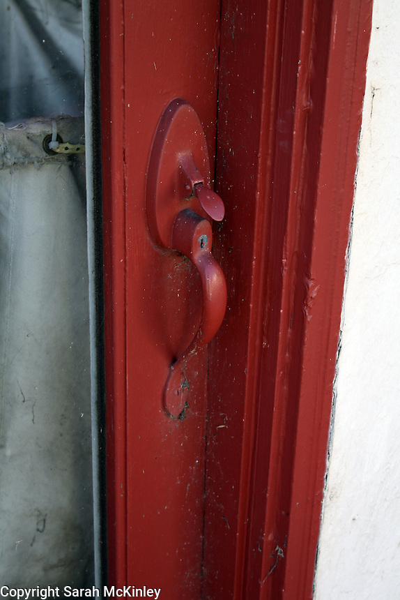 The red door handle of the red door to the abandoned Redwood Empire Cleaners in Willits in Mendocino County in Northern California.