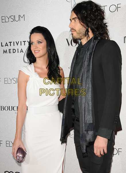 "RUSSELL BRAND.Art of Elysium 3rd Annual Black Tie charity gala '""Heaven"" held at 990 Wilshire Blvd in Beverly Hills, California, USA, .January 16th 2010 .half length white dress one shoulder silver clutch bag grecian couple black scarf jacket shirt blazer shiny beard facial hair profile.CAP/RKE/DVS .©DVS/RockinExposures/Capital Pictures"