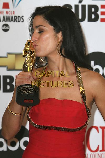 ANA ORTIS.2007 NCLR ALMA Awards - Press Room held at the Pasadena Civic Center, Pasadena, California, USA..June 1st, 2007.half length red gold halterneck straps hoop earrings award trophy kiss .CAP/ADM/CH.©Charles Harris/AdMedia/Capital Pictures *** Local Caption *** .