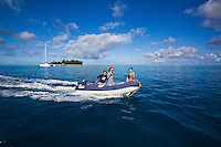 Family in dinghy at speed with woman taking picture off islet, with yacht in background