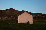 The gable end of a cottage pictured at sunset on the the Inner Hebridean island of Colonsay on Scotland's west coast.  The island is in the council area of Argyll and Bute and has an area of 4,074 hectares (15.7 sq mi). Aligned on a south-west to north-east axis, it measures 8 miles (13 km) in length and reaches 3 miles (4.8 km) at its widest point, in 2019 it had a permanent population of 136 adults and children.