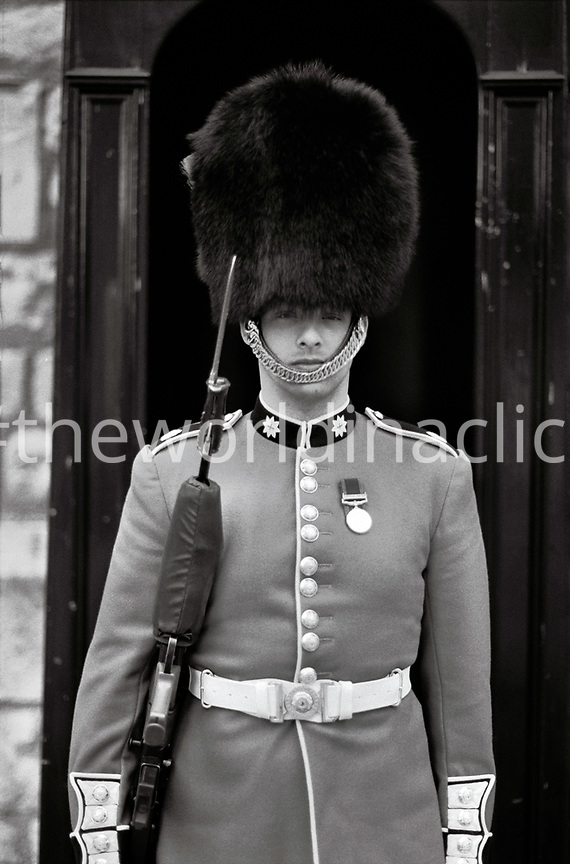 ENGLAND, London, a British Royal Guard stands on foot at the forecourt of Buckingham Palace (B&W)