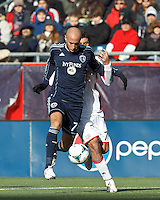Sporting Kansas City defender Aurelien Collin (78) and New England Revolution forward Juan Toja (7) battle for the ball.  In a Major League Soccer (MLS) match, Sporting Kansas City (blue) tied the New England Revolution (white), 0-0, at Gillette Stadium on March 23, 2013.