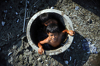 Boys in Besuki village cooling off in the village's old well, now polluted by mud. Since May 2006, more than 10,000 people in the Porong subdistrict of Sidoarjo have been displaced by hot mud flowing from a natural gas well that was being drilled by the oil company Lapindo Brantas. The torrent of mud - up to 125,000 cubic metres per day - continued to flow three years later.