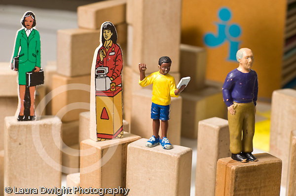 Education preschool 4 year olds still life closeup of human figures placed on top of wooden block structure by children horizontal