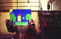 A girl shows her painting with the house of her dreams, Zen district, Palermo.<br /> Una bambina mostra il suo disegno con dipinta la casa che vorrebbe, quartiere Zen, Palermo.