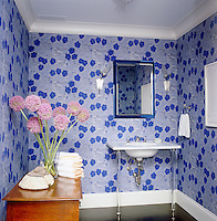 The walls of this small bathroom are enlivened with a vivid blue and white floral wallpaper
