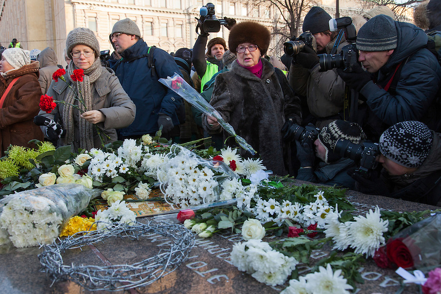 Moscow, Russia, 15/12/2012..Women lay flowers on a memorial to KGB victims in Lubyanka Square at an unauthorised opposition rally to mark a year of protests against Vladimir Putin.