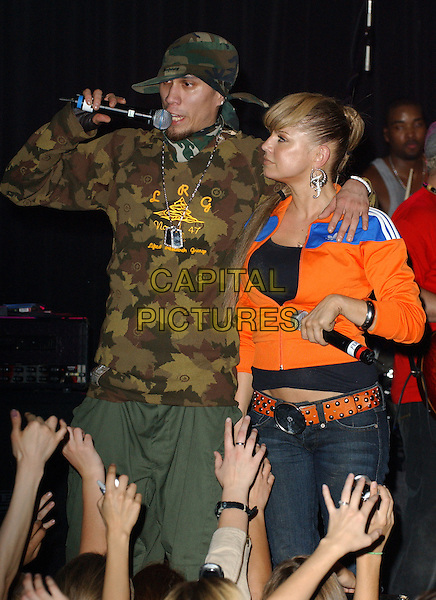 """TABOO & FERGIE - BLACK EYED PEAS.The Black Eyed Peas and Entertainment Industry Foundation Launch of The Pea Pod Foundation to Benefit """"A Place Called Home"""" held at The Key Club in West Hollywood ,California November 26th,2005.Ref: DVS.Stacey Ferguson half length on stage in concert gig performance music singing orange zip up zipper .www.capitalpictures.com.sales@capitalpictures.com.Supplied By Capital PIctures"""